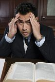 Portrait of a tensed male advocate sitting with book in the courtroom