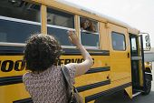 Rear view of woman waving good bye to her daughter in school bus