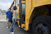 Young female student getting on school bus with classmate standing by it
