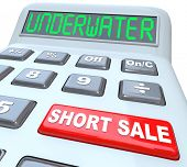 The word Underwater on a calculator digital display, symbolizing a home value being less than what is owed, and the words Short Sale on a red button symbolizing a solution to the problem