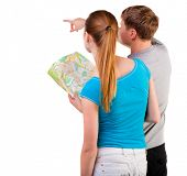 Back view journey of the young couple looking at the map. travelers man and woman in shorts consider
