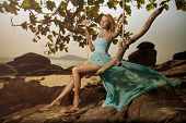 picture of flutter  - Beautiful Woman In Blue Fluttering Dress Swinging On A Beach Swing - JPG