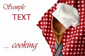 Whimsical cooking concept of vintage wooden spoon 'wearing' a chef's hat with red checkered napkin i
