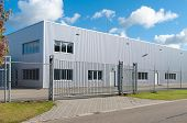 picture of workplace safety  - modern exterior of an industrial building surrounded by a fence with iron gate - JPG