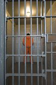 foto of prison uniform  - Rear view of a criminal standing behind bars - JPG