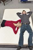Friends lying on mattress with hands behind head in furniture store