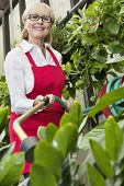 Portrait of a middle-aged female gardener spraying pesticide on plants in botanical garden