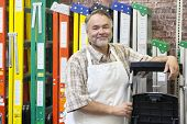 Portrait of happy middle-aged store clerk standing by multicolored ladders in hardware shop
