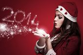 Beautiful brunette in the Santa costume blowing snowflakes and make New Year numbers 2014