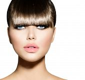 Fashion Model Girl With Trendy Hairstyle. Fringe. Haircut. Stylish Beauty Brunette Woman Face isolated on white background. Beautiful Make up. Vogue Style. Hair cut. Perfect Skin