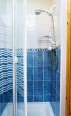 Modern Shower Cabin With Glass Doors In Blue And White