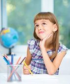 Little girl is drawing using color pencils and daydreaming while sitting at table, isolated over whi