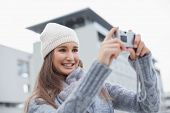 Smiling gorgeous woman with winter clothes on taking a self picture outdoors on a cold grey day