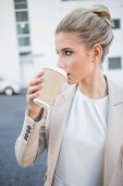 Relaxed stylish businesswoman drinking coffee outside on urban background