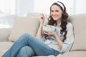 Pretty casual woman on cosy couch in bright living room eating salad