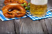 image of mug shot  - A beer mug and pretzels on napkins with blue and white rhombuses on a rustic wooden table
