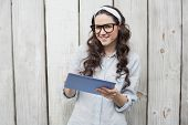 Smiling trendy woman with stylish glasses using her tablet while posing on wooden background