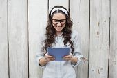 Trendy young woman with stylish glasses using her tablet while posing on wooden background