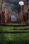 Steps leading to the ruins of an abbey at night with dark brooding sky