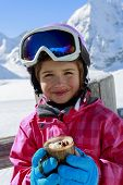 Apres ski, skiing, winter, child - young skier drinking hot chocolate  in winter resort
