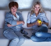 Mother with adult daughter watching television. Women looking film
