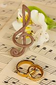 Treble clef, flower and wedding rings on musical background