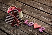 Open heart shaped Valentines Day gift box with heap of small hearts inside and word love on old wooden background.