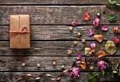 stock photo of wood craft  - Craft gift box with rose petals and dried flowers on old wooden plates - JPG