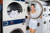 stock photo of laundromat  - Portrait of young woman in undergarments looking through washing machine lid at laundromat - JPG