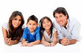 Happy Latinamerican family lying on the floor - isolated over white