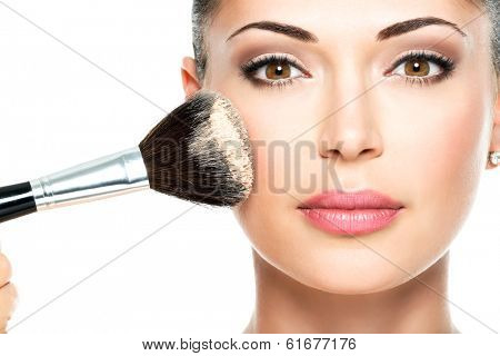 Closeup portrait of a woman  applying dry cosmetic tonal foundation  on the face using makeup brush. poster