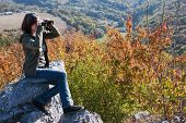 Beautiful Brunette With Binoculars Watching Autumn Nature