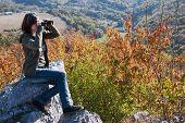 Beautiful Brunette With Binoculars Watching Autumn Nature