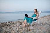 Постер, плакат: Woman talking skype at the beach