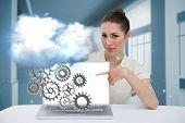 Digital composite of businesswoman pointing to her laptop showing cogs and wheels