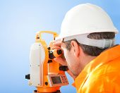 foto of land development  - Portrait of Senior land surveyor working with theodolite at construction site - JPG