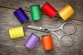 foto of wood craft  - Scissors and spools of colored thread on the wood background - JPG