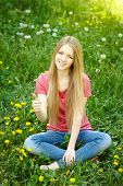 Smiling female sitting on the field of dandelions