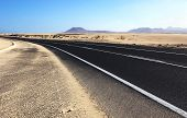 stock photo of long winding road  - Winding road through the dunes of Corralejo with volcano in the background in Fuerteventura Canary Islands Spain - JPG