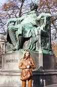 woman standing by Johann Wolfgang Goethe's statue, Vienna, Austria