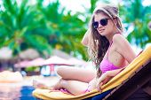 Happy young woman in bikini lying on chaise-longue luxury pool side