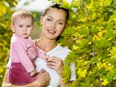 Portrait of beautiful happy smiling mather with baby outdoor, on nature