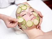 Beautiful young woman receiving facial mask of cucumber in beauty salon - indoors