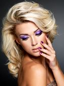 Beautiful blond woman with beauty purple manicure and makeup of eyes. Fashion model with curly hairs
