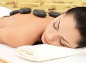 Stone massage for young woman at beauty spa salon. Recreation therapy.