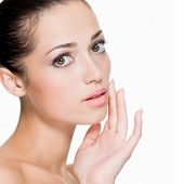 Closeup portrait of beautiful woman with fresh skin of face - isolated on white