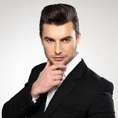 picture of enticing  - Fashion young businessman black suit casual  poses at studio - JPG