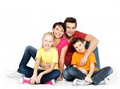 stock photo of cuddle  - Portrait of the happy  family with two children sitting at studio on white floor - JPG