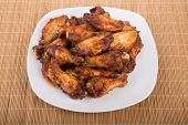 Mesquite Barbecue Chicken Wings On White Plate And Bamboo Mat