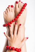 stock photo of toe nail  - Closeup photo of a female feet with beautiful red pedicure and big beads  - JPG